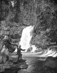 photo of fisherman casting at foot of falls